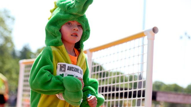 A boy runs in an alligator costume during the 33rd annual Awesome 3000 for the Salem-Keizer Education Foundation at McCulloch Stadium at Bush's Pasture Park in Salem on Saturday, May 2, 2015.