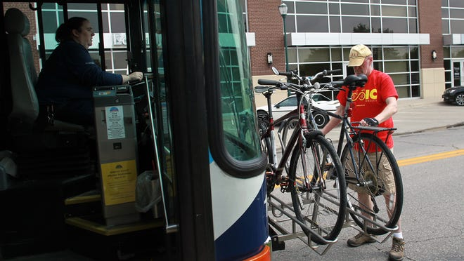 Iowa City Mayor Jim Throgmorton secures his bike onto a bus outside the Coralville Public Library during the annual bike, bus and car race on Monday, May 4, 2015.