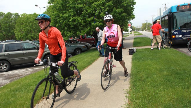 University Heights city councilor Virginia Miller, left, takes off down Fifth Street outside the Coralville Public Library during the annual bike, bus and car race on Monday, May 4, 2015. The race, which runs between Coralville and Iowa City's public libraries, encourages residents to use other forms of transportation, such as bikes and buses, which may not be much more time consuming than driving a car. David Scrivner / Iowa City Press-Citizen
