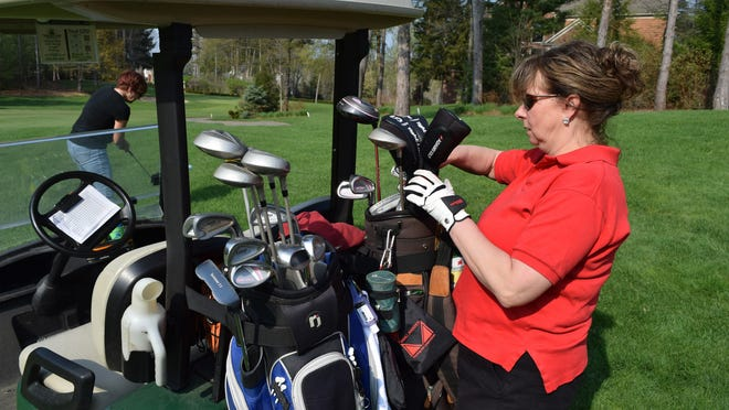 Roxanne Kania picks a club to play at Whispering Pines in Pinckney, which uses dynamic pricing.