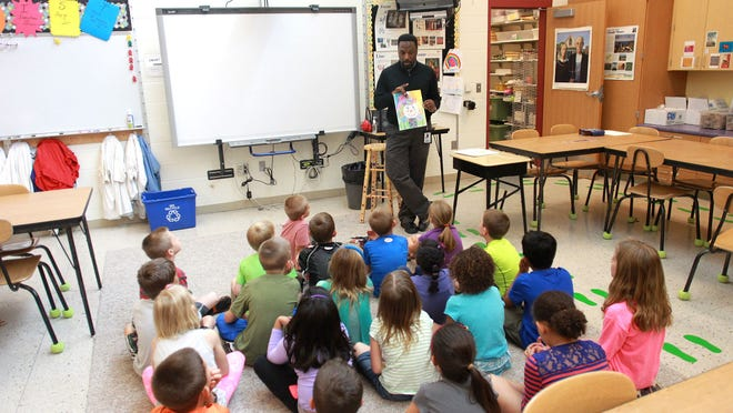 Art teacher Eugene Malone begins his first-grade class at Van Allen Elementary in North Liberty on Friday.