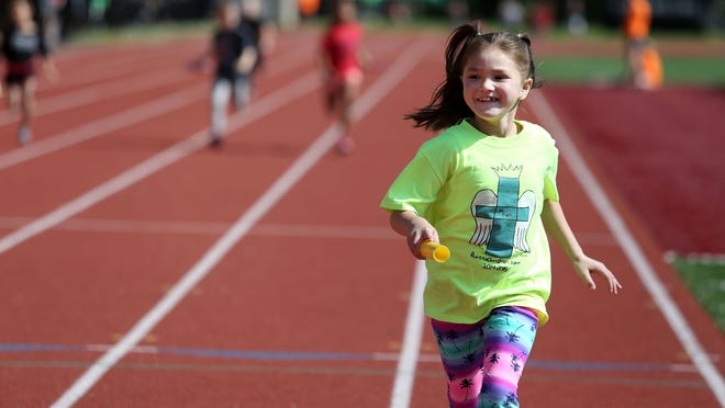 Riviera Christian School first-grader Carmen Pilgrim takes her team to victory during race in the Country Kids Relays on Saturday, May 9, 2015, in Salem, Ore.