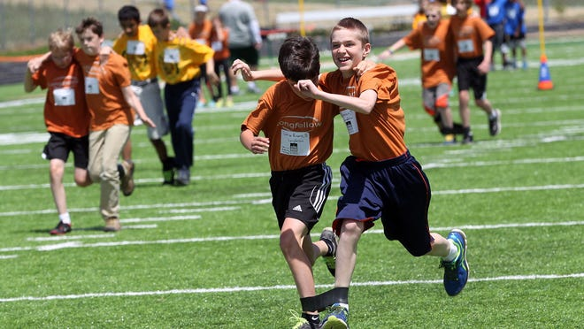 Longfellow Elementary sixth-graders Sebastian Loria-Eivins, left, and Tobey Epstein compete in the three-legged race on the final day of Elementary track and field day at West High on Wednesday.
