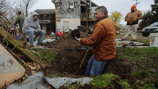 Dan Hill, 51, of Barry Township, center, looks over a piece of pottery he found digging out a pit that was once under an outhouse at the Hickory Corners home of John Rastoskey, 35, right. Bill Riley, 65, of Kalamazoo, left, takes a break from digging. The men are looking for antique bottles.