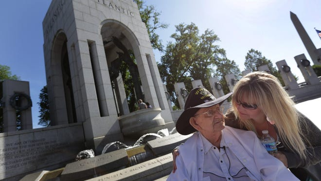 Fred Plichta of Monroe talks with Regina Johnson, also of Monroe, as they visit the National World War II Memorial in Washington, D.C. Johnson made the 88-year-old Army vet's dream of seeing the memorial — before macular degeneration steals his sight — come true Saturday.