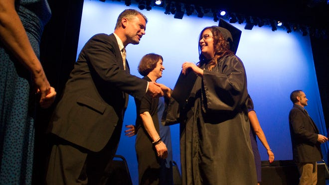 Graduating senior Dalia Garcia is congratulated by superintendent Stephen Murley at Tate High School's commencement ceremony at the Englert Theatre on Wednesday, May 27, 2015.
