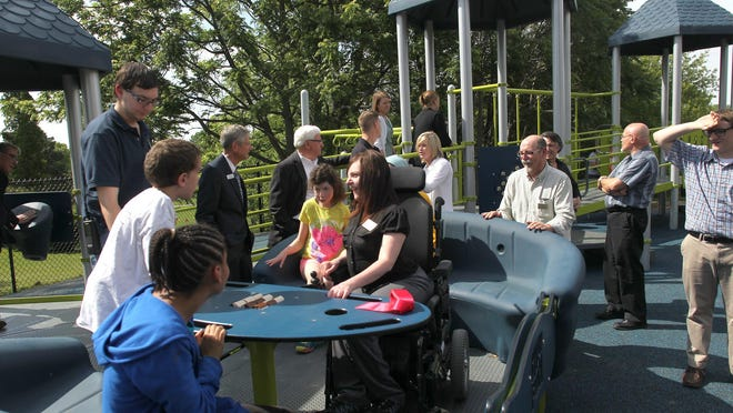 "Clients and friends try out the wheelchair-friendly ""Sway Fun Glider"" on the Arc of Southeast Iowa's new playground on Tuesday, June 2, 2015."