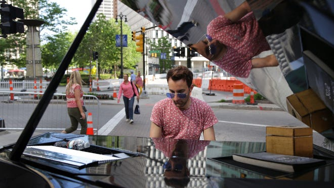 Davide Martello of Germany plays his piano by Campus Martius. Martello pulls his electronic baby grand by bike in cities around the world wherever, he says, he finds unusual buildings to serve as backdrops. He uses a trailer attached to his 1991 Volkswagen Corrado between cities.