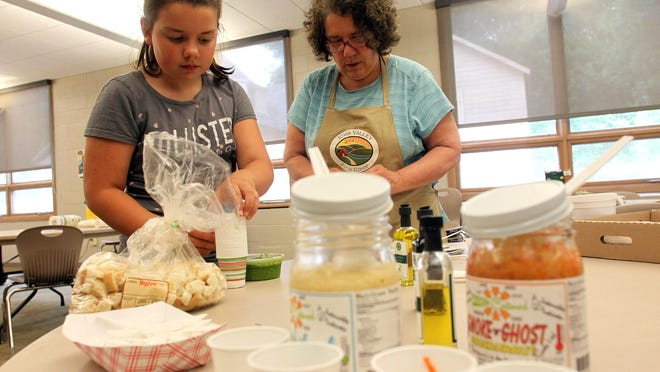Evelyn Bergus, 9, and her grandmother, Rebecca, prepare samples for the Iowa Valley Food Co-op's open house at Zion Lutheran Church on Wednesday, June 3, 2015. David Scrivner / Iowa City Press-Citizen