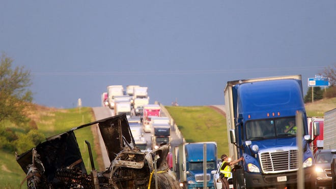A police officer checks on truck driver Dennis Holcomb, 53, of Sumner, S.C. following a multi-car accident on Interstate Highway 80 west of Williamsburg on Friday, May 8, 2015.