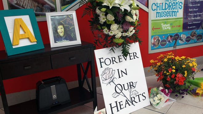 Flowers and photos rest outside the Iowa Children's Museum during a public memorial for Andrea Farrington in Coralville on Sunday, June 14, 2015. David Scrivner / Iowa City Press-Citizen