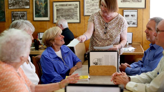Statesman Journal reporter Carol McAlice Currie gives Gannett grants to community leaders at the Statesman Journal's Holding Court at the Court Street Dairy Lunch in downtown Salem on Tuesday, June 16, 2015.