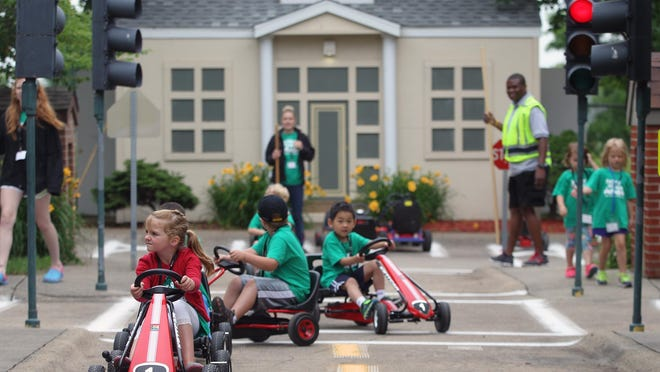Gracie Van Tassell leads a group of children through Safety Village outside Grant Wood Elementary on Wednesday. The camp is in its 20th year of operation.
