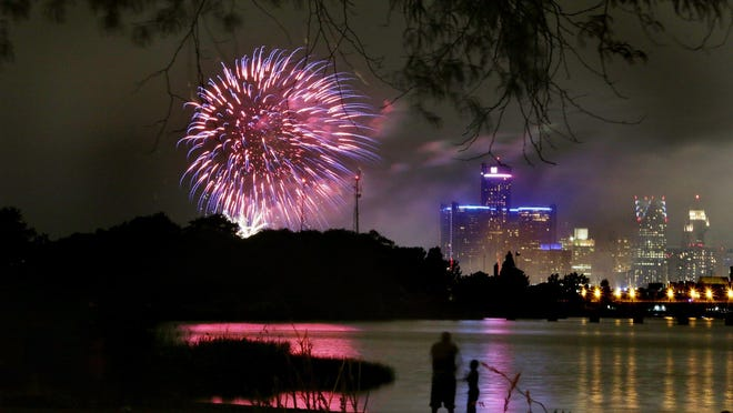 People watch the Ford Fireworks from the beach on Belle Isle last summer.