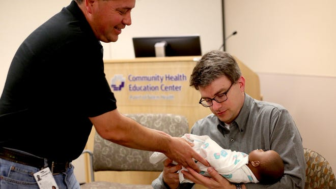 Instructor Larry Kramer gives Steven Marlowe, of West Salem, a doll to practice with during the Boot Camp for New Dads on Monday, June 15, at Salem Hospital.