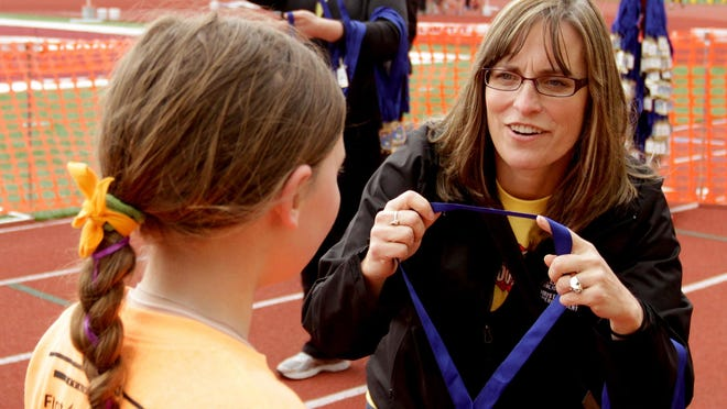 Salem-Keizer Public Schools Superintendent Christy Perry awards a medal to a runner during the 33rd annual Awesome 3000 for the Salem-Keizer Education Foundation at McCulloch Stadium at Bush's Pasture Park in Salem on May 2.
