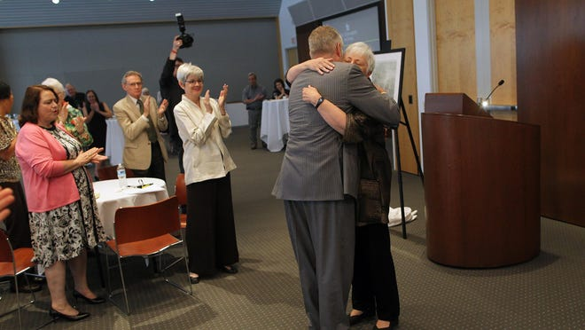 Retiring University of Iowa President Sally Mason hugs her husband, Ken, during a farewell ceremony Wednesday at the Levitt Center on the UI campus.