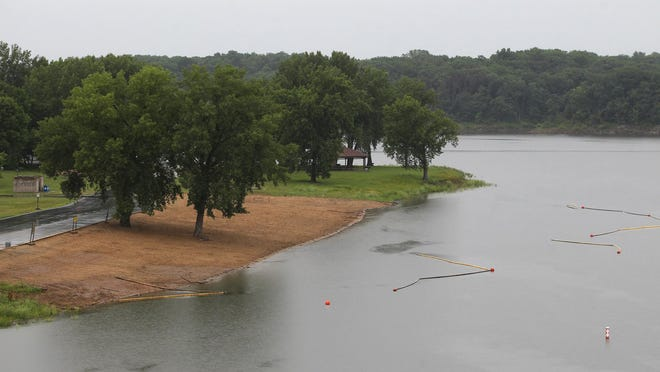 Rain comes down over the West Overlook Beach on Wednesday. Persistent rain in the past week has caused the water level at Coralville Lake to climb, putting some campsites and beaches in jeopardy of closing as the Fourth of July holiday approaches.