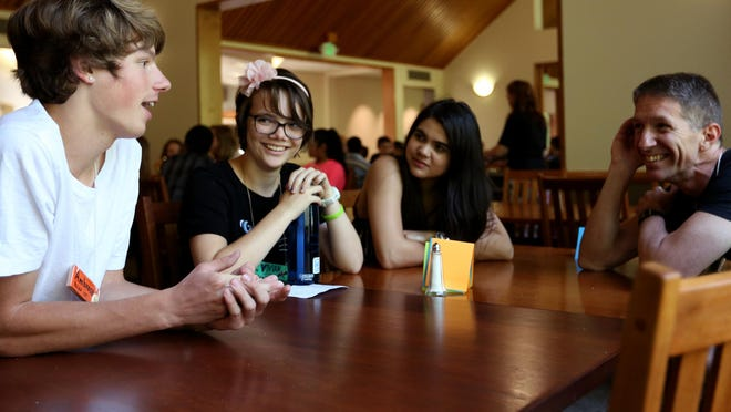 Ambrose Philipek (from left), 17, of Salem, Vivian Britton, 14, of Tigard, Theresa Thurston, 18, of Salem and instructor David York, of Beaverton hang out during a break at the Young Musicians & Artists summer camp at Willamette University.