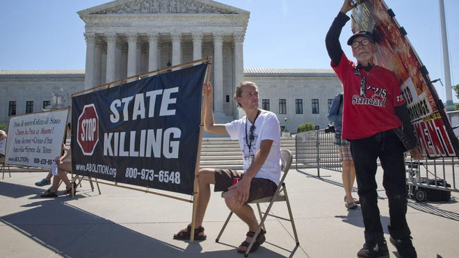 Jack Leason, 19, of Wellington, New Zealand, helps hold a protest sign at a rally against the death penalty Monday outside the Supreme Court.