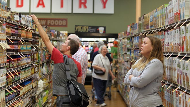 Shoppers browse the aisles of Lucky's Market during an early opening for friends and family on Monday.