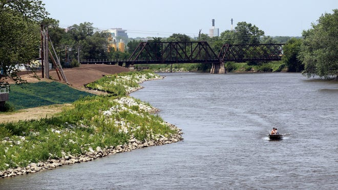 A boat passes the levee behind Thatcher Mobile Home Park near McCollister Boulevard on June 3.