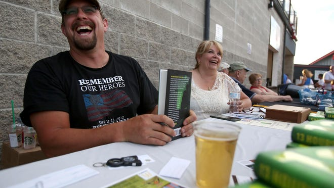 "John ""Tig"" Tiegen jokes with a visitors as he signs copies of 13 Hours In Benghazi, Tiegen fought in the Battle of Benghazi. Photo taken on Saturday, July 4, 2015, in Keizer, Oregon."