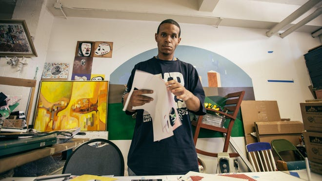 James Johnson, 24, of Inkster MI shuffles papers for cut outs for the upcoming art event 24 June 2015.