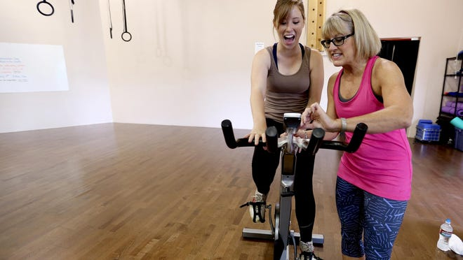 Statesman Journal reporter Natalie Pate, left, gets help from instructor LaDonna Smith setting up her stationary bike during the Pedal to the Finish: A Ride to End Cancer, a fundraiser for the American Cancer Society, at Epic Fitness in Salem on Saturday, July 11, 2015.