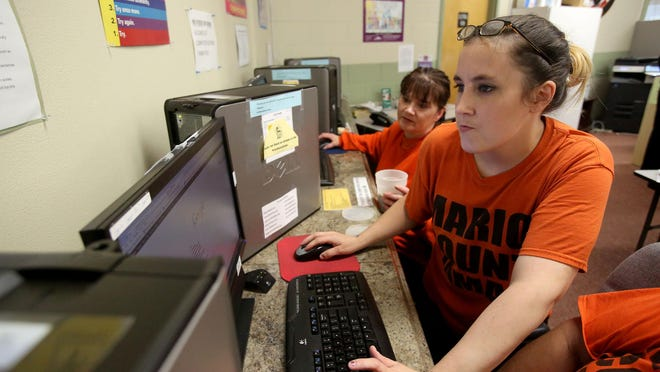 Marion County inmate April Gysin helps a fellow inmate log on to a computer Friday, July 10, at Community Action's De Muniz Resource Center in Salem.