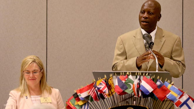 Rotary Club of Salem President Mary Way, left, listens as Lavaud Cheristin, with the Rotary Club in Hinche, Haiti, speaks on building wells in the area with the help of the Rotary Club of Salem during a meeting at the Salem Convention Center on Wednesday, July 15, 2015.