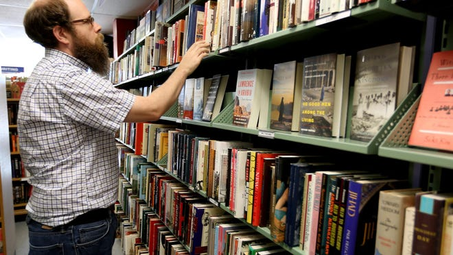 Obadiah Baird, 35, helps a customer find a book in the downtown Salem location of The Book Bin on July 2, 2015. Book Bin's Lancaster store has closed.