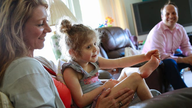Bella Chinonis, 6, sits on the lap of her mom, Ida Chinonis, as dad Denny Chinonis looks on at their home.