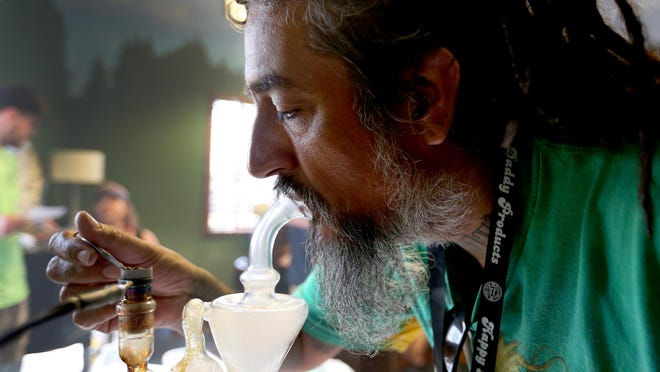 Dominic Zuniga, 43, of Monmouth, smokes hash oil as a judge July 10 during the 710 Festival at the Patient Grower Network (PGN) Lodge in Keizer.