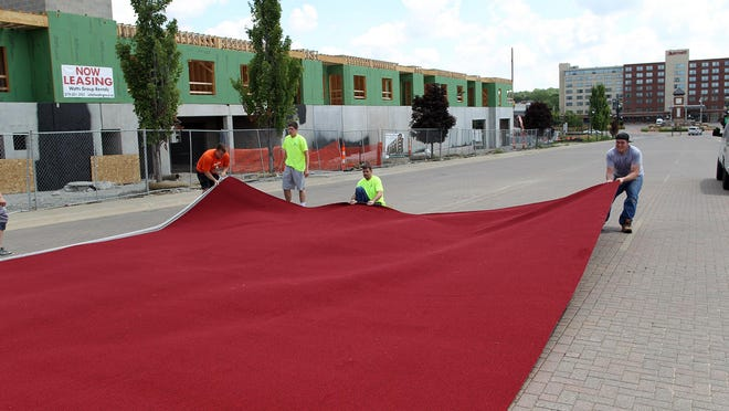 Randy's Carpets employees stretch the red carpet down the Iowa River Landing on Thursday in preparation for RAGBRAI.