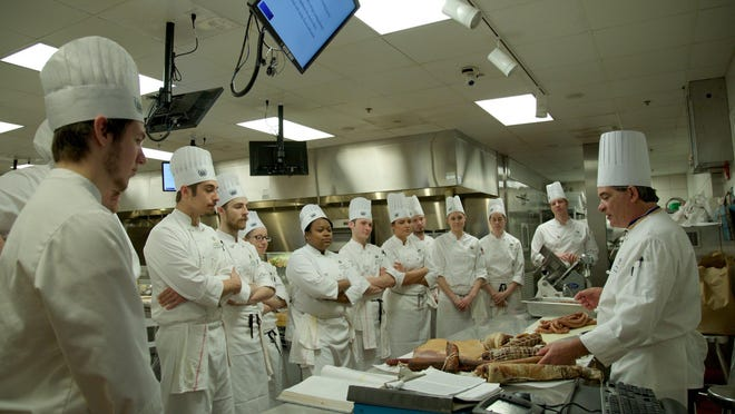 Second-year culinary students at Schoolcraft College watch former restaurant owner and chef Brian Polcyn of Milford demonstrate meat cutting in their charcuterie class.