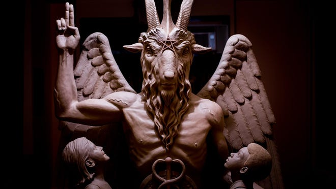 A bronze Baphomet, depicting Satan as a goat-headed figure with two children