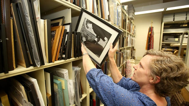 Mary McRobinson, Willamette University archivist, retrieves a photo of Sen. Mark Hatfield meeting the Shaw of Iran in 1970. The image is part of the universities Mark O. Hatfield collection.