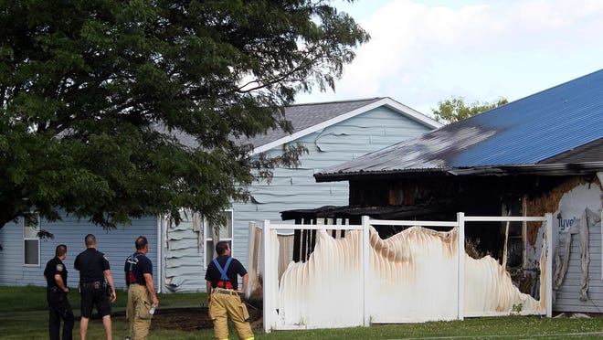 Firefighters and police officers inspect the damage of a house fire on Indigo Court on Tuesday, Aug. 11, 2015. No injuries were reported.