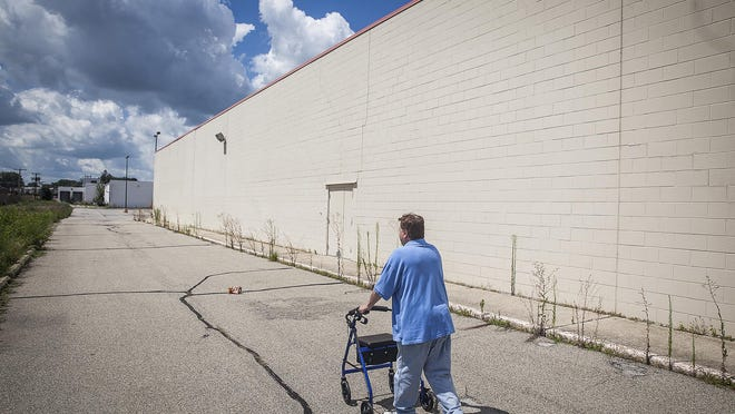 Mike Fields, a resident of Cambridge Square apartments who was diagnosed with ALS, uses his walker to cross the empty lot of the former Kmart before crossing McGalliard Road to reach Dollar General Tuesday, Aug. 11.
