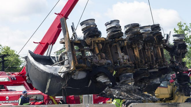 A wrecker lifts the damaged gasoline tanker truck that flipped over a retaining wall and burned on I-75 in Lincoln Park near the Detroit border.