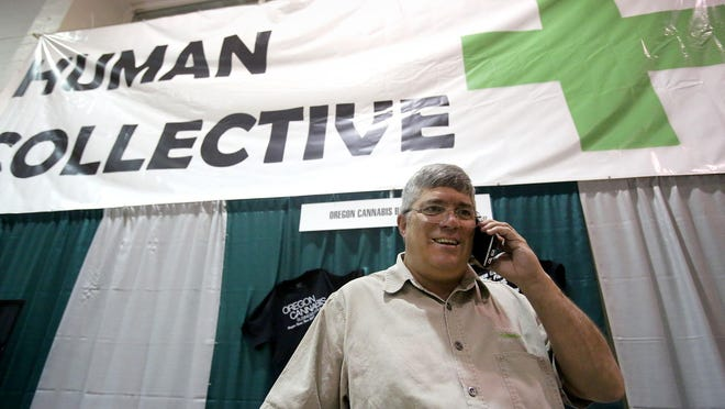 Donald Morse, Director of the Oregon Cannabis Business Council, fields a call at the organization's booth during the Oregon State Fair on Friday, Aug. 28, 2015, Salem, Ore.
