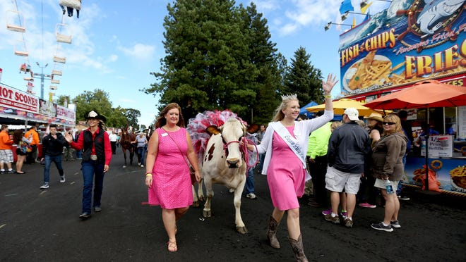 Emma Miller, the 2015 Oregon Dairy Princess, waves to the crowds while guiding Flower, a cow in a tutu and tiara, during a livestock parade at the Oregon State Fair in Salem on Saturday, Aug. 29, 2015.