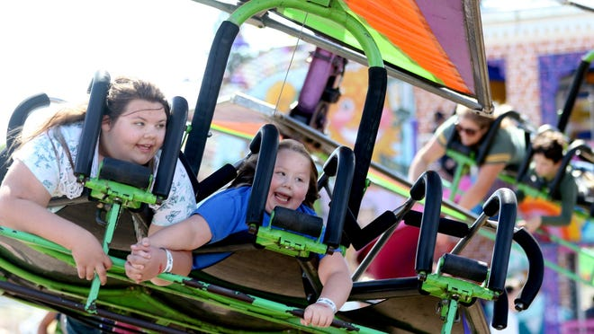 """Sisters Julie Jeffrey, 13, and Kaity Jeffrey, 7, of Portland, ride the Cliff Hanger on Salem at the 150th Oregon State Fair. """"My stomach felt weird,"""" Kaity said after the ride."""