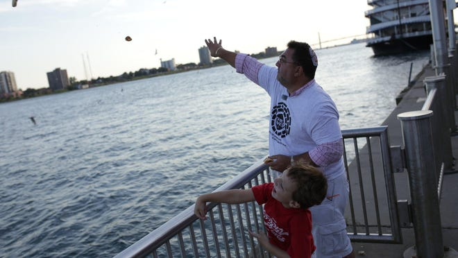 Robby Cantor of Huntington Woods and his father Neil Cantor of Huntington Woods tosses bread with Jewish Community members dispose of bread crumbs into the Detroit River as part of the Tashlich ritual on Tuesday September 15, 2015 while observing a Rosh Hashanah tradition for the Jewish New Year. Disposing of the crumbs during the annual ritual symbolizes the casting-away of shortcomings from the previous year.