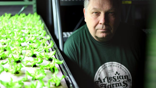 """Jeff Adams displays lettuce trays at Artesian Farms, an indoor hydroponic farm in the Brightmoor neighborhood in Detroit. """"We can scale this up throughout the city and then we can start to get all of our food locally as opposed to bringing in it in from California, Arizona,"""" he said."""