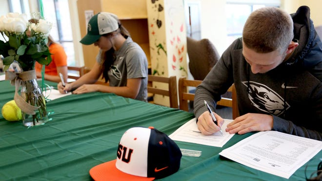 Andy Armstrong, right, signs a letter of intent to play baseball for Oregon State University, as Tayler Gunesch signs to play softball with Portland State University during a signing day ceremony at West Salem High School on Thursday, Nov. 12, 2015.