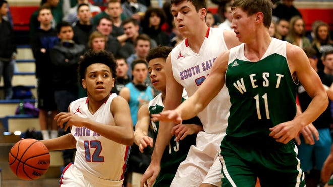South Salem's Jaden Nielsen Skinner (12) moves with the ball past teammate Christian Russell (21) and West Salem's Isaiah Pineda (13) and Jared Oliver (11) in the first half of the West Salem vs. South Salem boy's basketball game at South Salem High School on Tuesday, Dec. 15, 2015.