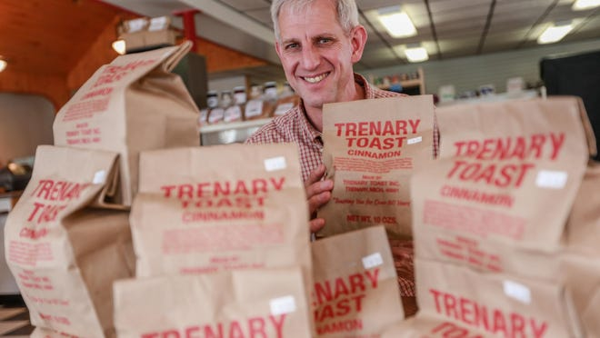 """Trenary Home Bakery owner Andy Reichert, 50, of Chatham, stands behind bags of the hard cinnamon toast at the Trenary Toast Café on Nov. 17. """"It is a mission,"""" Reichert says of producing the U.P. favorite."""