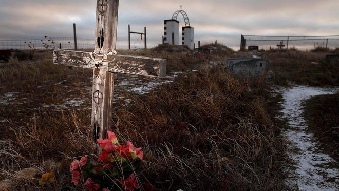 A cross marks a grave at the Wounded Knee National Historic landmark in South Dakota, where about 150 of the 300 Lakota men, women and children killed by the 7th Cavalry in 1890 are buried.